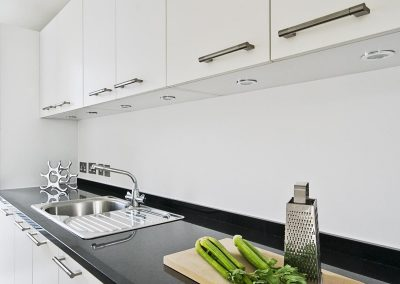 contemporary white kitchen with black granite worktop