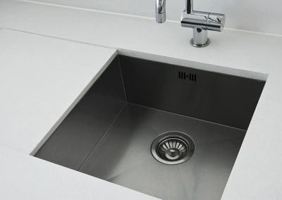 detail of a rectangular designer kitchen sink with chrome water tap