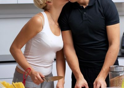 Playful young couple in their kitchen making dinner